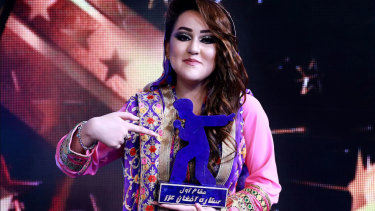 "Zahra Elham holds the trophy she won in the television music competition ""Afghan Star"" in Kabul."