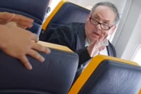 A man yells racist insults at a woman sitting in the same row on a Ryanair flight, while a fellow passenger tries to intervene. YouTube David Lawrence