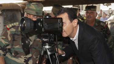 Syrian President Bashar al-Assad, centre, uses a military telescope during a visit to a strategic town in Idlib province last week.