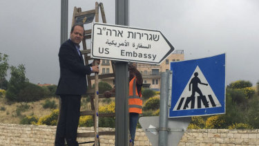 Jerusalem Mayor Nir Barkat poses with a new road sign to the US embassy in Jerusalem.