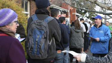 Josh Frydenberg hands out flyers to voters outside a polling station in 2016.