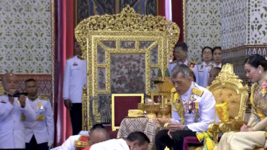 In this image made from video, Thailand's King Maha Vajiralongkorn, centre, and Queen Suthida, right, are greeted by Thai Prime Minister Prayuth Chan-ocha, bottom front, during the second of a three-day coronation ceremony.