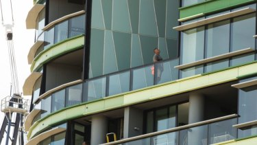 Tradesmen work on Opal Tower in Olympic Park.