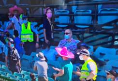 Ben Grogan, wearing sunglasses and a Hawaiian shirt, watches on as police remove spectators from the SCG on Sunday.