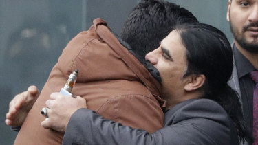 Abdul Aziz, centre, a survivor of the Linwood mosque shootings, is embraced by friends outside the Christchurch District Court.