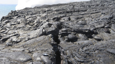 a crack that has developed near the site of a lava stream pouring out of a lava tube on the sea cliff at the Kamokuna ocean entry at the Hawaii Volcanoes National Park on the Big Island of Hawaii.
