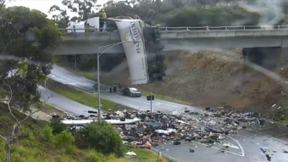 Truck left dangling from overpass shuts freeway