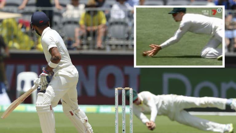 Fine margins: Peter Handscomb takes a catch off Virat Kohli in controversial circumstances.