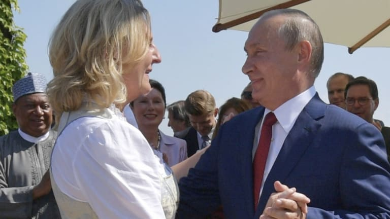 Russian President Vladimir Putin, right, congratulates Austrian Foreign Minister Karin Kneissl as he attends the wedding of Kneissl with Austrian businessman Wolfgang Meilinger in Gamlitz, southern Austria.