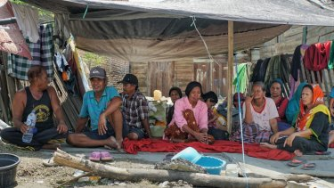 Sangati, far right, and neighbours sit under a tarpaulin that will serves as shelter also at night.