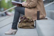 Unrecognizable woman sitting on stairs and reading book, bag on foreground
