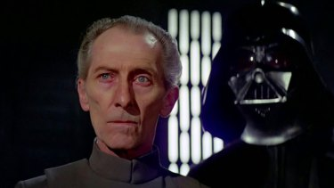 Peter Cushing as Grand Moff Tarkin in the original Star Wars, flanked by Darth Vader.