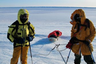 Expeditioners from Davis station haul a sled.