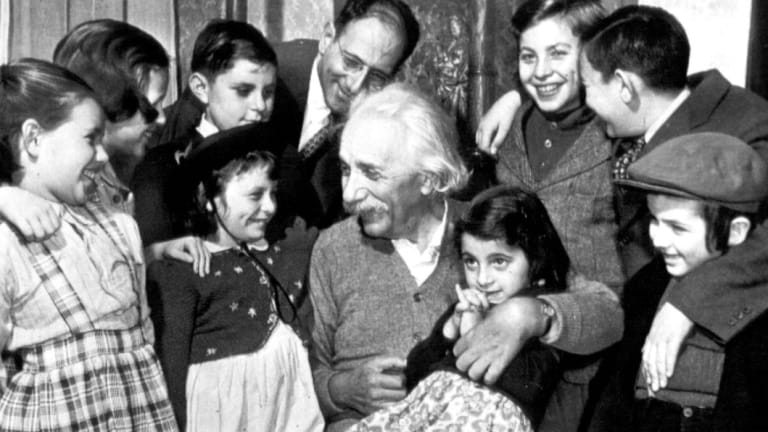 Displaced migrant children from a shelter visit Einstein for his 70th birthday in New York in 1949.