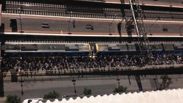 Crowds wait in the sun at South Yarra station.