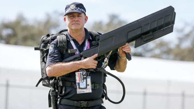 Queensland Police senior sergeant John Hildebrand carrying DroneShield's drone gun, which was used at the Commonwealth Games.