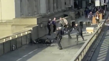 In this grab taken from video,, a man is surrounded by police after an incident on London Bridge.