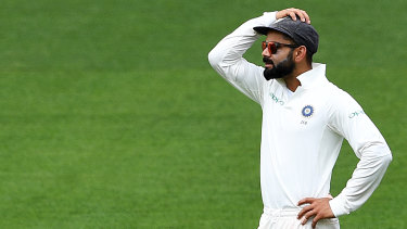 Complication: Virat Kohli reacts as the Australian tail wags a little too vigorously for his liking.