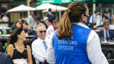 A social distancing officer patrols the Everest Race Day at Royal Randwick Racecourse on October 17, 2020 where almost 11,000 people gathered following approval of COVID-safe plans.