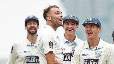 Got him: NSW teammates get around Harry Conway after dismissing Victoria's Travis Dean.