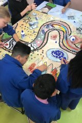 Children at St Georges Road Primary School in Shepparton making a mosaic from the painting they created for the Dunggula digital touch book.