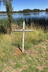 A metal cross near on the shores of Lake Ginninderra.