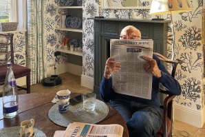 Rupert Murdoch captured in his element: reading one of his many newspapers at home.