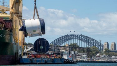 A part of the tunnel boring machine named Kathleen is lifted onto a barge from a ship at White Bay.