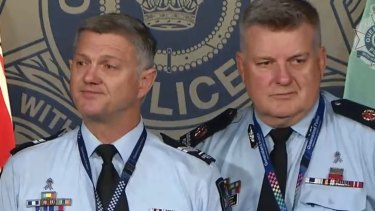 Queensland Senior Constable Neil Scutts, left, fights back tears as he fronts media with Assistant Commissioner Mike Condon.