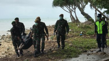 Indonesian officials find a body on the beach at Tanjung Lesung, one of the hardest hit villages.