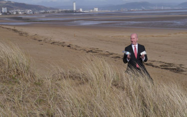 British Labour MP Geraint Davies collects plastic rubbish washed up on Swansea Beach in Wales.