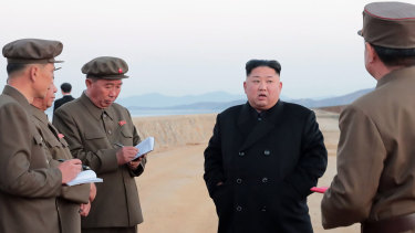 Kim Jong-un, centre, listens to a military official as he inspects a weapon testing at the Academy of National Defence Science, North Korea.