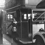 A conductress punches the Bundy clock from the double-decker bus number 201 in October 1942.