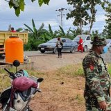 A road checkpoint in Baucau, Timor-Leste, where vehicles are sprayed inside and out, and a tank provides hand-washing water.