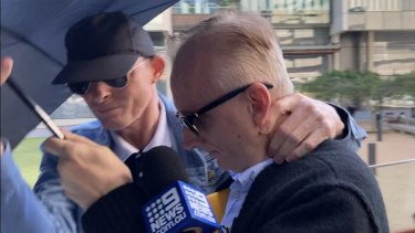Neville WilliamGentry (right) leaves Brisbane Magistrates Court on Monday with his protective umbrella.