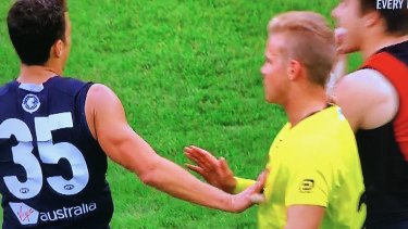 Ed Curnow makes contact with an umpire during the match against Essendon.