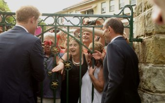 Prince Harry and former prime minister Tony Abbott greet wellwishers at the gate to Kirribilli House.