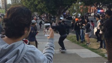 Skateboarders move the informal competition to a footpath, away from a tense standoff with police on the road.