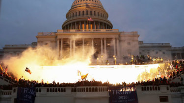 A flash lights up the front of the US Capitol as a mob of Trump supporters control the steps of the building.
