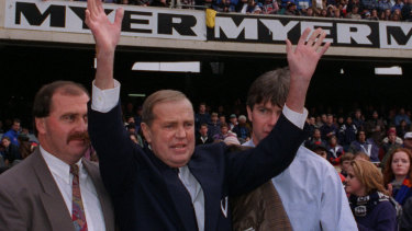 Ted Whitten, supported by his son (left) and Frawley (right), waves to the MCG crowd at the 1995 State of Origin clash.