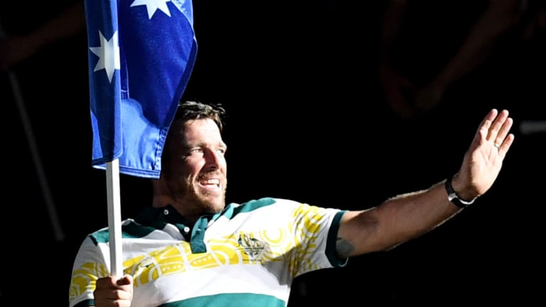 Kurt Fearnley carries the Australian flag into the closing ceremony.