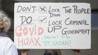 One of the signs at the anti-lockdown rally at Parliament House in Melbourne.