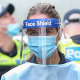 Medical staff wearing PPE holding material about to walk into the Flemington public housing flats on Sunday.