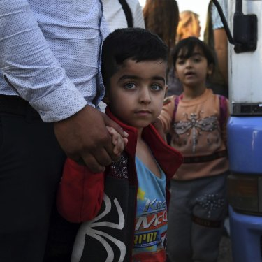 A Syrian boy holds his father's hand after disembarking from one of the buses that brought 784 Syrian refugees to Bardarash Refugee Camp in Iraqi Kurdistan.