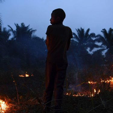 Former child soldier Wilson, 15 years old, watches over a small fire in his village in Kasai Central.