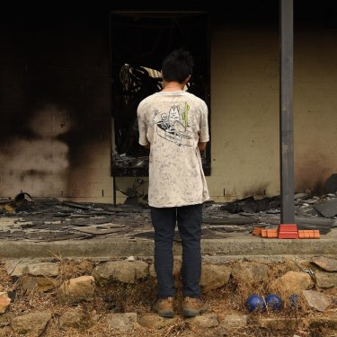 Balmoral resident Gabriel aged 16 looks into what was his bedroom at his home. It was destroyed by fire on December 21.