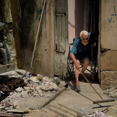 Abdulsalam Abdulqadir, 73, sweeps outside his gate from his wheelchair as an air strike hits nearby in West Mosul, Iraq, in October 2017.
