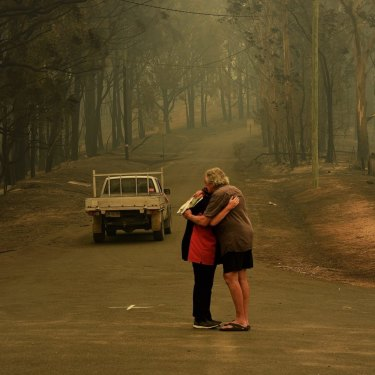 Residents comfort each other on Runniford Road in Nelligen where several homes were destroyed in January 2020.