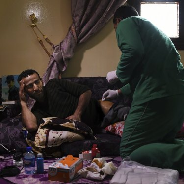 Syrian Democratic Forces soldier Shiyar Noushtiman has his wound dressed at a house in Hasaka where SDF soldiers are recuperating from injuries sustained fighting IS.