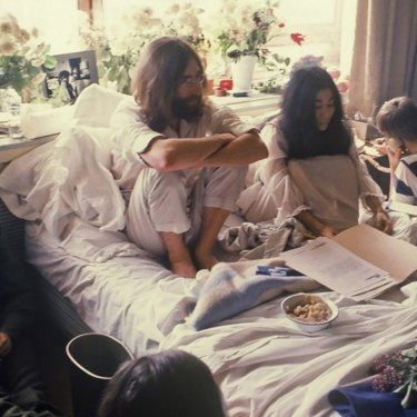Ritchie Yorke with notebook (left) beside John Lennon and Yoko Ono in 1969.